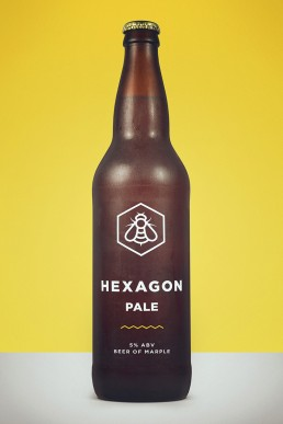 a mockup of a brown glass bottle, branded with Hexagon Pale graphics printed on a transparent label