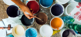A man dipping a paintbrush into a paint container, taking brown paint